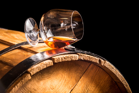Glass of cognac on the old wooden barrel photo