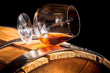 glass  reflection: Glass of cognac on the old wooden barrel