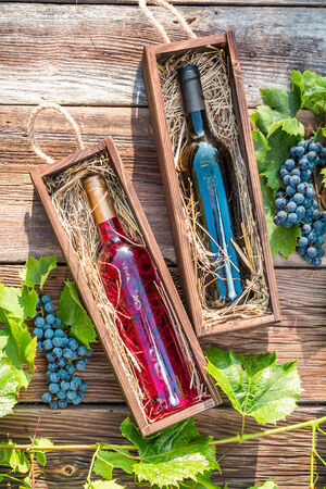 Different types of wine in a wooden box and grapes photo