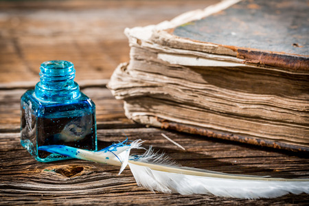 White feather on blue inkwell and old book photo