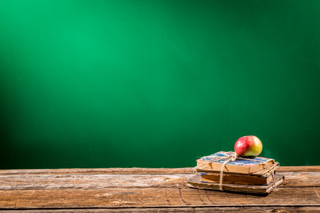Stack of books and an apple in a classroom photo