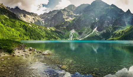 mountains and sky: Crystal clear mountain lake and rocky mountains Stock Photo