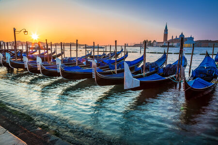 Blue gondolas at sunrise in Venice photo