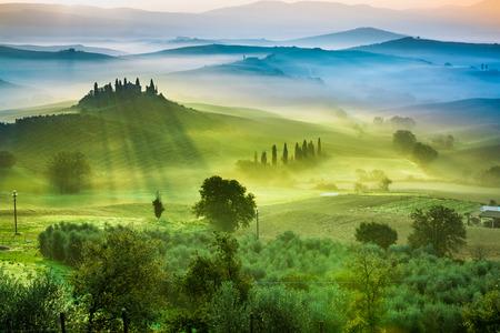 Schöne Aussicht auf grüne Felder und Wiesen bei Sonnenuntergang in der Toskana