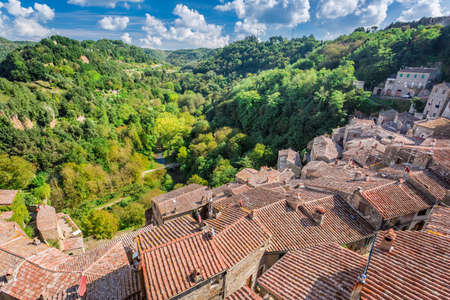 View of a green valley in Sorano over red roofs, Italy photo