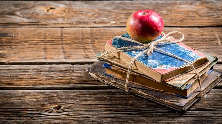 Livros velhos e maçã na mesa da escola