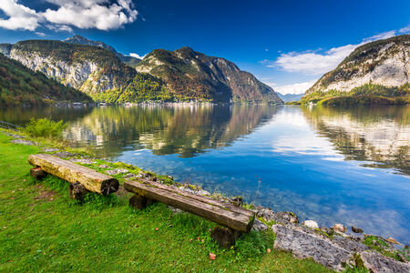 Wooden bench at mountain lake in the Alps photo