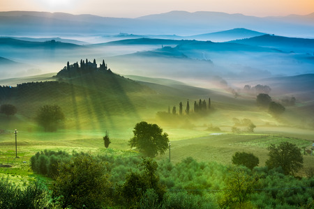 Beautiful view of green fields and meadows at sunset in Tuscany 스톡 콘텐츠
