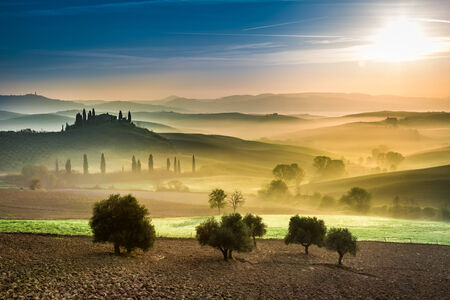 Gold and green fields in the valley at sunset, Tuscany photo
