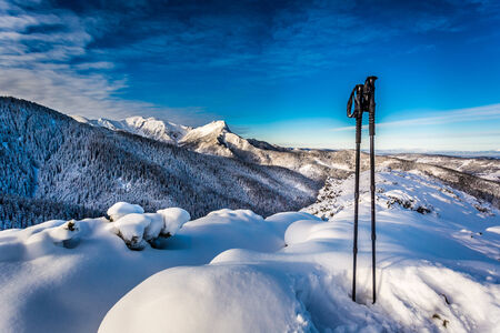 Ski poles at the top at sunrise in winter