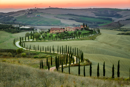 Sunset and winding road with cypresses in Tuscany Stockfoto