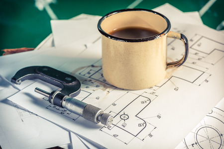 micrometers: Micrometers, mechanical diagrams and a cup of coffee Stock Photo