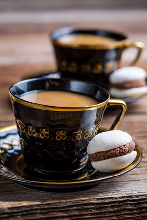Nut-chocolate macaroons and coffee for dessert photo