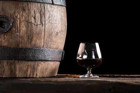 Glass of cognac and old wooden barrel