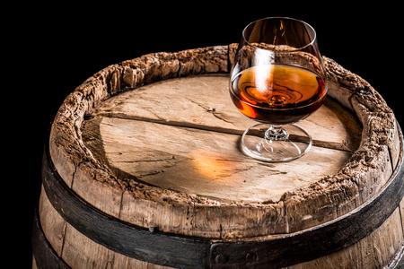 Glass of cognac on old oak barrel photo