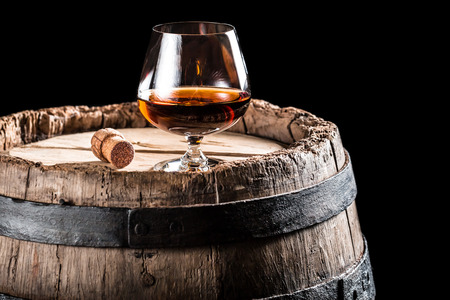 Glass of cognac on old wooden barrel photo