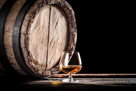 Old barrel and a glass of cognac