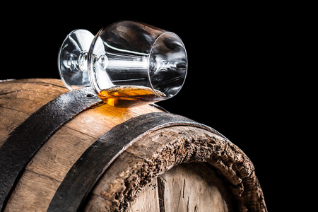 Old oak barrel and a glass of cognac photo