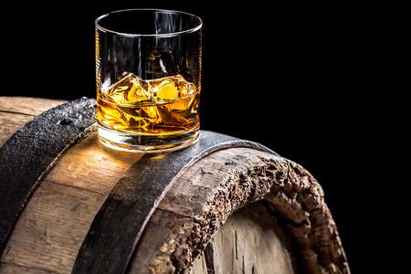 古いオーク材の樽に氷を入れたウイスキーのガラス