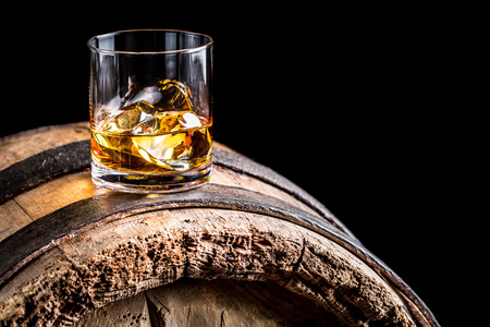 Glass of whisky with ice on old wooden barrel photo