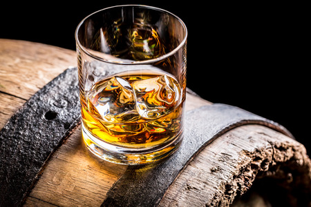 Glass of whisky and old wooden barrel photo