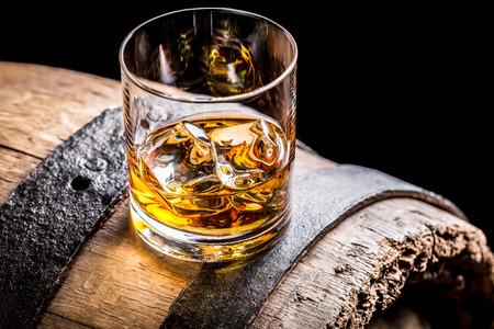Szklanka whisky i stara drewniana beczka