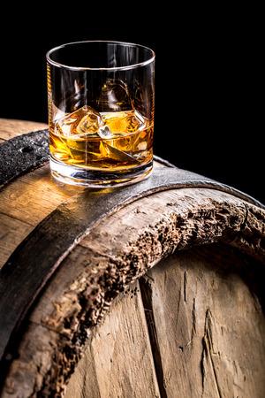 Whisky glas en oude houten vat