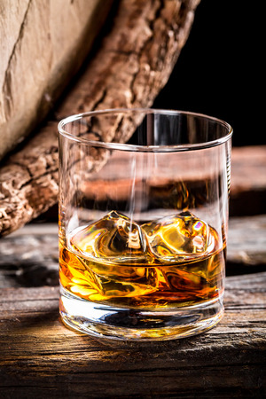 Glass of whisky and old oak barrel