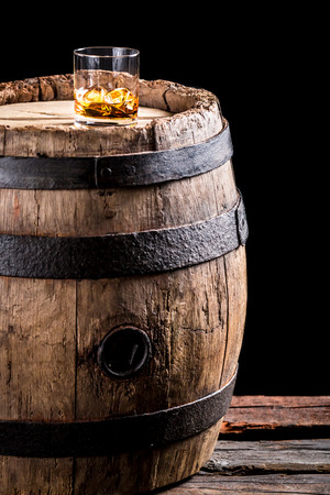 Glass of aged brandy or whiskey on the rocks and old oak barrel Banque d'images