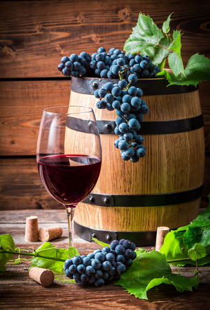 demijohn: Glass of red wine and grapes