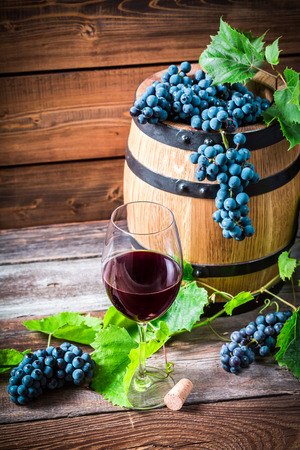 demijohn: Glass of red wine and grapes in a wooden cellar