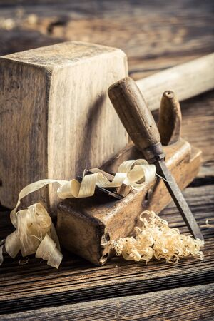 carpenter's sawdust: Wooden hammer, planer and chisel on a carpentry workbench