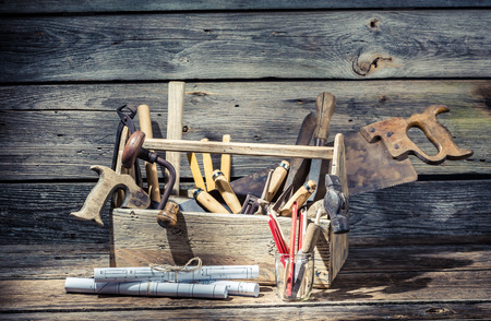 toolbox: Hammer, saw and paper scheme in the carpentry toolbox
