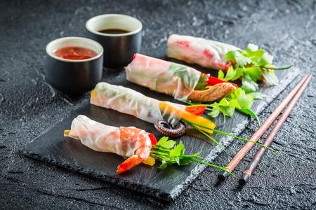 mariscos: Los rollitos de primavera con verduras, mariscos y salsa Foto de archivo