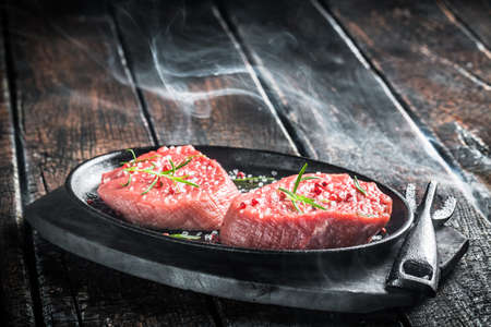 Grilling fresh piece of red meat with herbs photo
