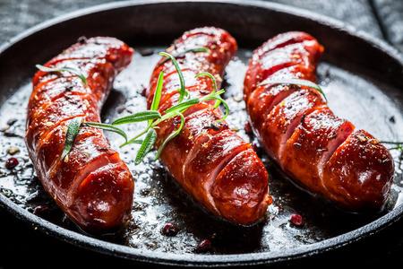 Grillad korv med färsk rosmarin på het grill maträtt Stockfoto