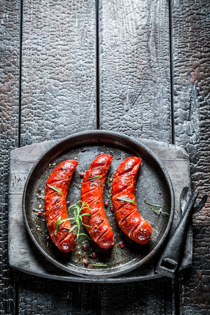 Grilled sausage with fresh herbs on hot barbecue dish Standard-Bild