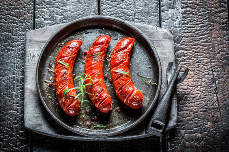 cooked sausage: Roasted sausage with fresh herbs on hot barbecue dish