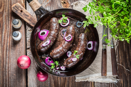 fresh meat: Hot black pudding with onion and parsley Stock Photo