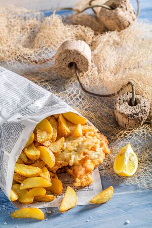 Homemade fish cod with chips in newspaper photo