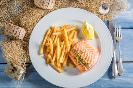 Tasty salmon with chips with lemon photo