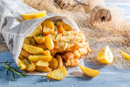 Tasty fish and chips served in paper with lemon photo