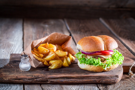 Tasty burger  with fries in old wooden board
