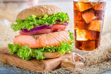 salmon fishery: Fresh fishburger with salmon  served with cold drink Stock Photo
