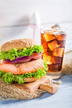 salmon fishery: Tasty fishburger with salmon  served with cold drink