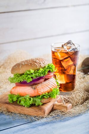 salmon fishery: Homemade burger with fish  served with cold drink Stock Photo
