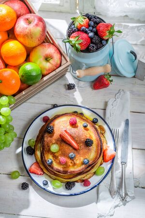 Sweet pancakes with maple syrup and fruits photo