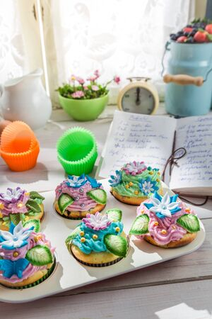 Decorating fresh muffins with sweet cream photo