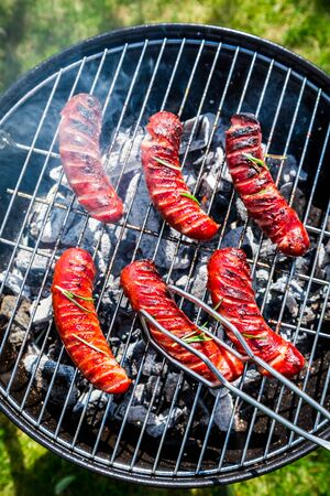Roasted sausages with rosemary on garden grill photo