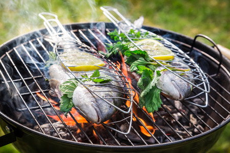 Grilling tasty fish with herbs and lemon photo